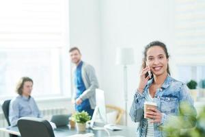 aufgeregter moderner Büroleiter, der am Telefon freundlich spricht foto