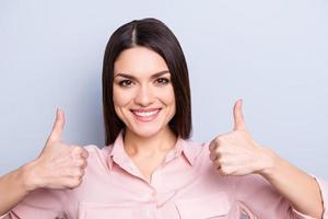 Porträt der hübschen, charmanten, trendigen, niedlichen Frau im klassischen Hemd, das zwei Daumen oben mit den Fingern zeigt, die Kamera lokalisiert auf grauem Hintergrund betrachten foto