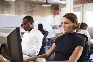 Geschäftsleute, die an Computern im geschäftigen modernen Büro arbeiten foto