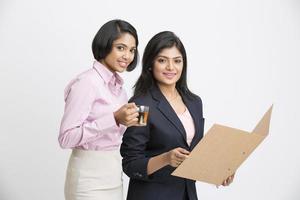 schöne junge zwei indische Geschäftsfrauen, die mit Dokument aufwerfen foto
