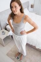Porträt einer fitten Frau, die auf Skala im Schlafzimmer steht foto
