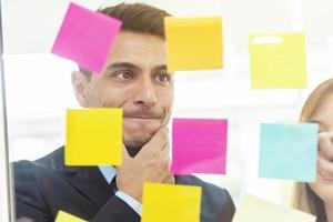 Nahaufnahme des Geschäftsmannes, der auf Notizblock auf Brillenfenster denkt und schaut. foto
