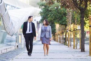 ernsthafter Geschäftsmann, der Ideen mit Kollegen während des Spaziergangs teilt foto