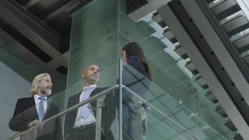 Führungskräfte diskutieren über Geschäfte in modernen Bürogebäuden foto