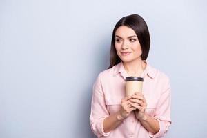 Porträt mit leerem Platz der verträumten nachdenklichen niedlichen trendigen Frau, die Becher mit warmem Tee in Händen betrachtet, die Kopienraum lokalisiert auf grauem Hintergrund betrachten foto