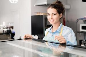 lächelnde Frau, die im Café arbeitet foto