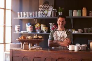 Porträt des männlichen Kaffeehausbesitzers, der hinter Zähler steht foto