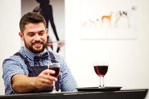 Barmann, der Rotwein in Gläsern an einer Funktion dient foto