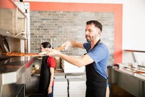 Restaurantkoch nimmt frisch gebackene Pizza aus dem Ofen foto