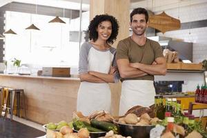 Porträt des Paares, das Bio-Lebensmittelgeschäft zusammen läuft foto