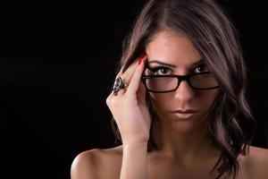 schöne brünette junge Frau, die Dioptrienbrille trägt foto
