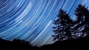 Sternspur. Nachthimmel über Bergwald.
