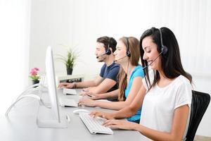fröhliche junge ethnische weibliche Betreiberin mit Headset, die mit Kunden in einer Kundendienst-Hotline am Telefon anruft foto