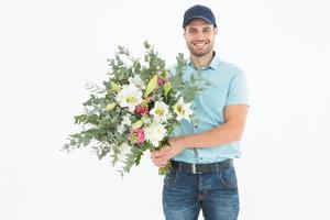 glücklicher Lieferbote, der Blumenstrauß hält foto