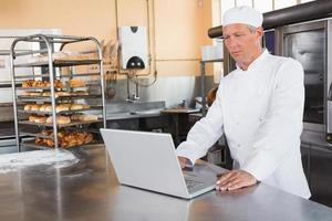 fokussierter Bäcker mit Laptop auf Arbeitsplatte foto