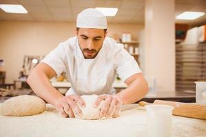 Bäcker knetete Teig an einer Theke foto