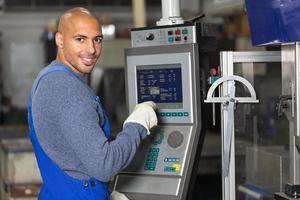 Arbeiter, der eine Maschine mit Bedienfeld bedient foto