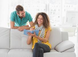 lächelnde Frau auf der Couch zeigt ihrem Kollegen ihr Notizbuch