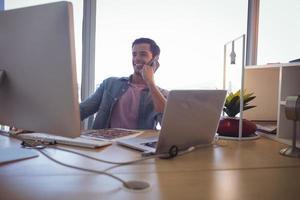 junger Geschäftsmann, der am Handy spricht, während er im Büro arbeitet foto