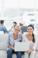 Frauen, die Laptop mit Kollegen im Hintergrund am kreativen Büro verwenden foto