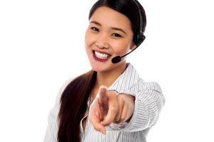 Callcenter-Supportmitarbeiter zeigen in Richtung Kamera foto