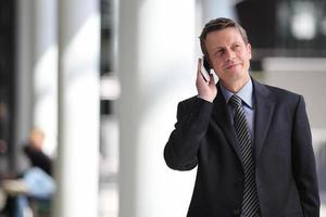 lächelnder Geschäftsmann, der am Telefon spricht foto