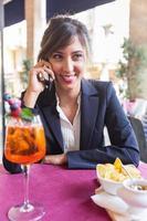 junge Geschäftsfrau, die während einer Pause auf dem Mobiltelefon spricht foto