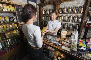 Verkäufer, der Produkt an Kundin im Teeladen gibt foto