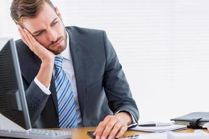 nachdenklicher Geschäftsmann, der am Schreibtisch sitzt foto
