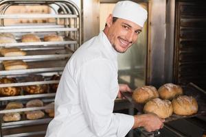 glücklicher Bäcker, der frische Brote herausnimmt foto