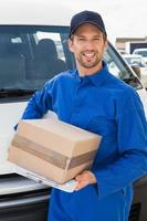 Zustellfahrer lächelt in die Kamera von seinem Van, der Paket hält foto