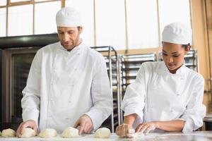 Team von Bäckern, die Teig vorbereiten foto