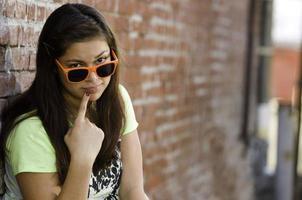 süßes hispanisches junges junges Mädchen, das neugierig in die Kamera schaut foto