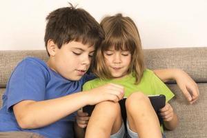 Kinder spielen mit einem digitalen Tablet foto