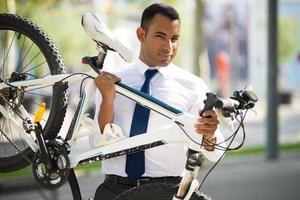 hübscher Büroangestellter, der sein kaputtes Fahrrad trägt foto
