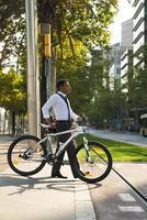 ernsthafter Büroangestellter mit Fahrradkreuzungsstraße foto
