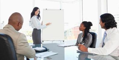 Drei ernsthafte Mitarbeiter hören einer Präsentation aufmerksam zu foto