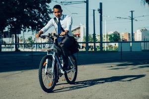 junger lateinamerikanischer Büroangestellter, der Fahrrad zur Arbeit fährt foto