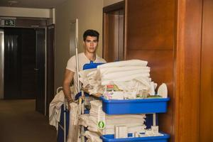 junger Mann, der einen Reinigungswagen im Hotel schiebt foto