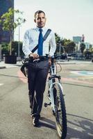 selbstbewusster Mann mit dem Fahrrad, das über Straße geht foto