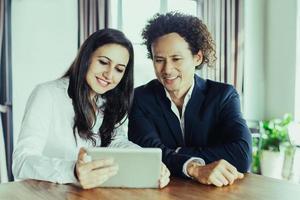 fröhliche Geschäftsleute diskutieren Daten auf Tablet foto