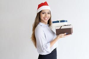 lächelnder Weihnachtsbüroassistent, der Geschenke trägt foto