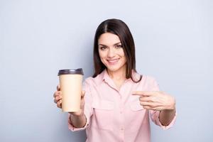 Porträt der hübschen, charmanten, positiven Frau, die Becher mit Tee in der Hand zeigt mit Zeigefinger, der Kamera lokalisiert auf grauem Hintergrund zeigt foto