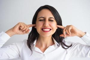 genervte Geschäftsfrau, die Ohren mit den Fingern stoppt foto