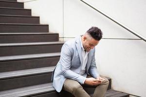 aufgeregter hübscher Geschäftsmann, der SMS am Telefon liest foto