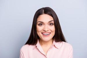 Porträt der hübschen, charmanten, niedlichen, netten, herrlichen Frau im klassischen Hemd, das mit gesundem weißem strahlendem Lächeln lacht, lokalisiert auf grauem Hintergrund, der Kamera betrachtet foto