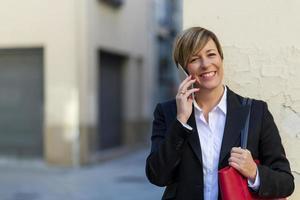 Exekutive, die am Telefon spricht und Kamera auf der Straße betrachtet foto