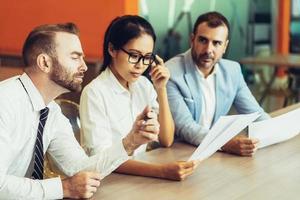 Drei ernsthafte Geschäftsleute lesen und diskutieren Dokumente