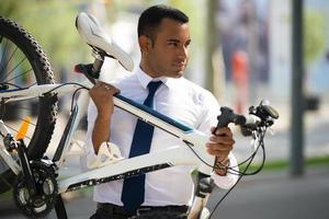 hübscher hispanischer Büroangestellter, der sein Fahrrad trägt foto