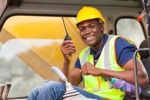 afrikanischer Bulldozer-Betreiber, der auf Walkie-Talkie spricht